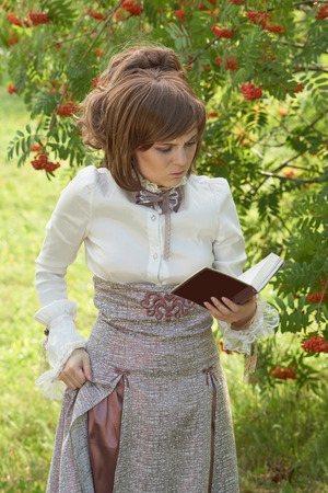 bourgeoisie: Girl gets angry while reading book. She wears retro style clothes. Stock Photo