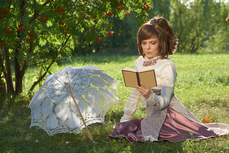 bourgeoisie: Girl in retro style dress reads book in the park with sun umbrella beside her