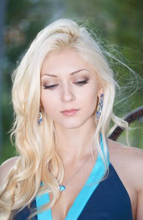 blue dress: Portrait of the beautiful blonde girl in blue dress in the park Stock Photo