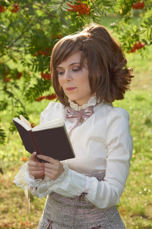 bourgeoisie: Dressed in retro clothes beautiful girl reads book with slight smile on her face