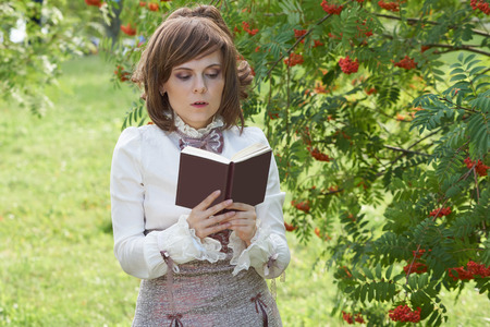 bourgeoisie: Girl dressed in retro style reads interesting book. Her mouth is slightly open