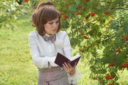 bourgeoisie: Beatiful girl found something interesting in the book while reading outdoors Stock Photo