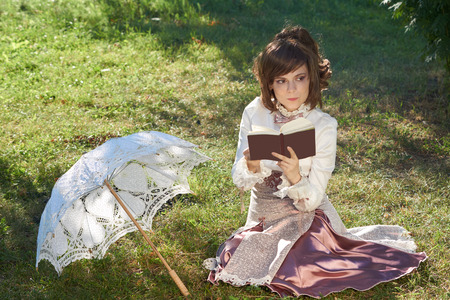 bourgeoisie: Girl in retro style dress thinks about the novel that she reads outdoors