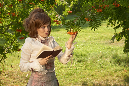 bourgeoisie: Vintage style girl holds book in right hand and rowan berries in the other.