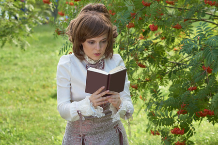 bourgeoisie: Beatiful girl reads book in the park Stock Photo