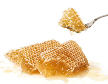 honey comb: Spoon of raw honey over pieces of honey comb