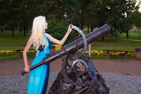 gazer: Young girl in blue dress with long blonde hair stands by the minument of metal telescope as if adjusting it