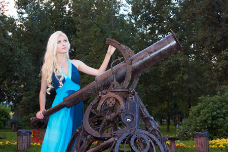 gazer: Young beautiful girl stands by the telescope and looks to the sky