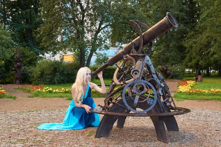 gazer: Attractive young girl looks through telescope in the park Stock Photo