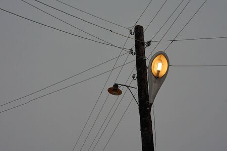 Pillar with energy saving street lamp in the village and powerlines crossing