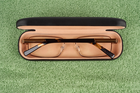 nearsighted: Spectacles in case on green terry background