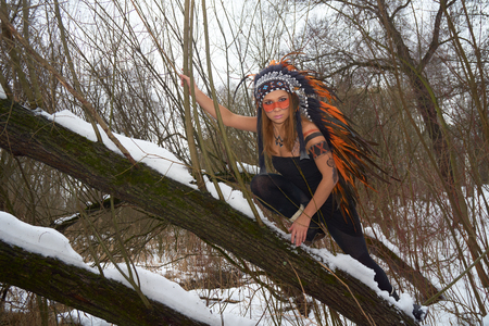 native american headdress: Girl in native american headdress climbs tree