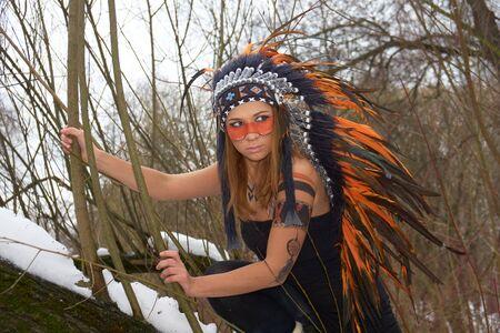 native american headdress: Girl in native american headdress on the tree in winter forest