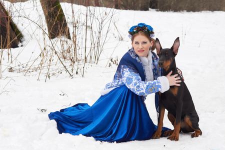 doberman pinscher: Young russian woman in traditional winter clothing with Doberman Pinscher