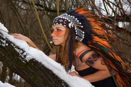 girl models: Girl in native american headdress climbs tree