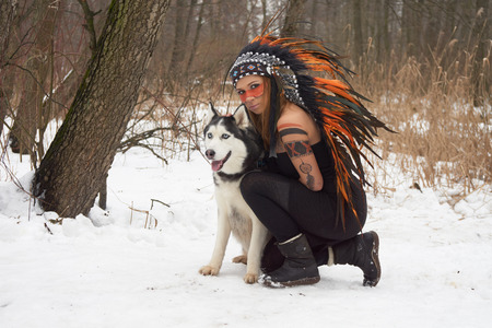 native american headdress: Girl in native american headdress with Siberian Husky Stock Photo