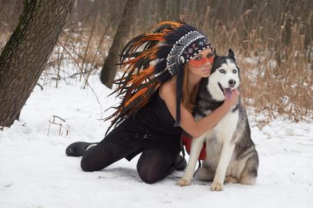 native american headdress: Girl in native american headdress embraces her Siberian Husky