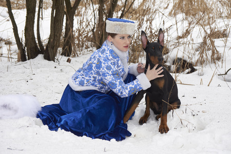 pinscher: Young russian woman in traditional winter clothing with Doberman Pinscher