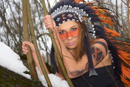 indio americano: Chica en el tocado del nativo americano en el �rbol en el bosque de invierno