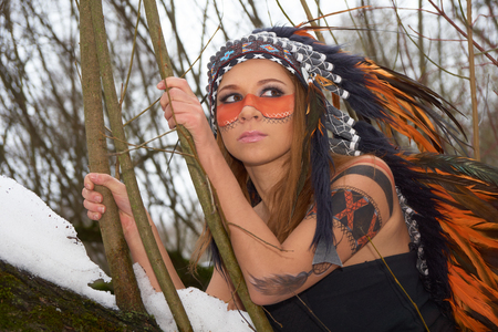native american girl: Girl in native american headdress on the tree in winter forest