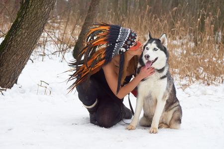 native american headdress: Girl in native american headdress likes her Siberian Husky