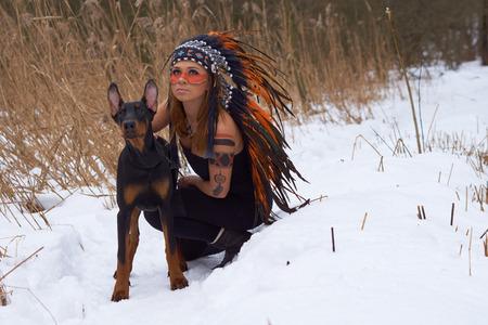 native american headdress: Girl in native american headdress with Doderman Pinscher Stock Photo