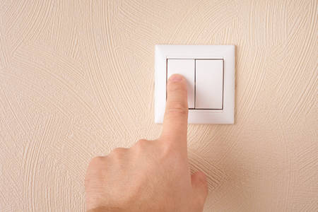 forefinger: Mans hand switches light at his home by forefinger Stock Photo
