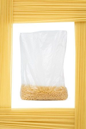 framed: Pasta in open plastic pack framed by capellini (pasta). Food concept