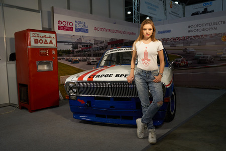 april 15: Moscow Crocus Expo, Moscow, Russia - April 15, 2016: Girl stands near old car at Photoforum 2016
