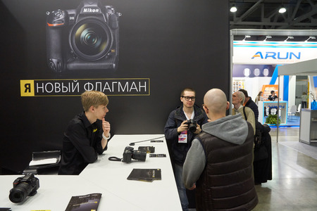 distributor: Moscow Crocus Expo, Moscow, Russia - April 15, 2016: Visitors trying Nikon cameras at Nikon Distributor company Photo Sale at Photoforum 2016