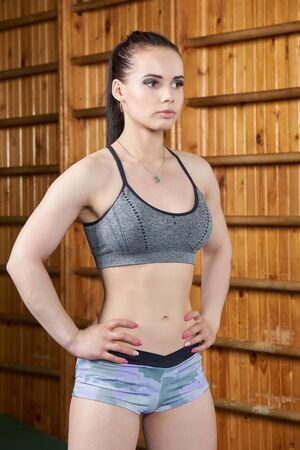 wall bars: Beautiful young girl before fitness exercise near wall bars in the gym