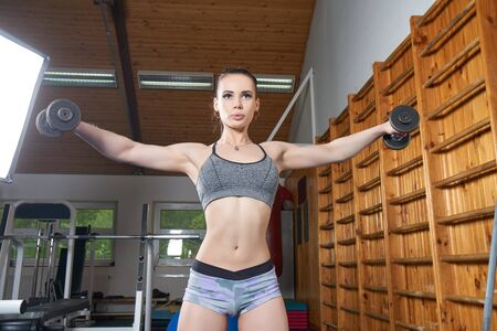 wall bars: Beautiful young girl exercising with dumbbells near wall bars in the gym