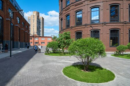 backstreet: Moscow, Russia - June 01, 2016: Reconstructed red brick buildings on the territory of former Arma factory with fresh green bush on the forground. Nizhniy Susalniy pereulok (lane) in Moscow. Editorial