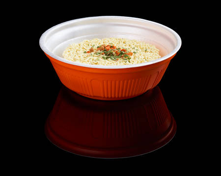 reflecting: Instant noodles in plastic plate isolated on black reflecting background