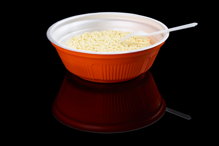 reflecting: Instant noodles in red plastic plate with one plastic fork isolated on black reflecting background