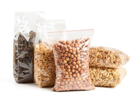 Gedroogde vruchten en noten in transparant pakket over wit van links naar rechts: gedroogde moerbei, geroosterde en gezouten pinda's, hazelnoten, walnoot en cashewnoten op de bodem