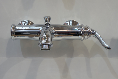 exposición: Glossy metal mixer mounted to white wall in the bathroom Foto de archivo