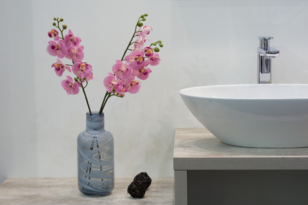 White top ceramic washbasin, glossy metal mixer and a bunch of artificial flowers on the left