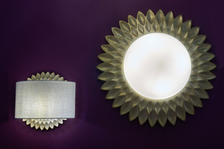 Two decorative switched on lamps mounted on dark violet wall with lampshades