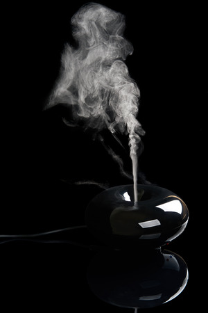 air diffuser: Black plastic aroma diffuser with streaming smoke on black reflecting background Stock Photo