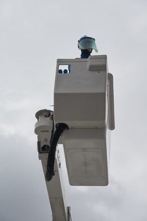 An electrician (dummy) in protective uniform works on insulated aerial platform designed to work safely on electric power lines