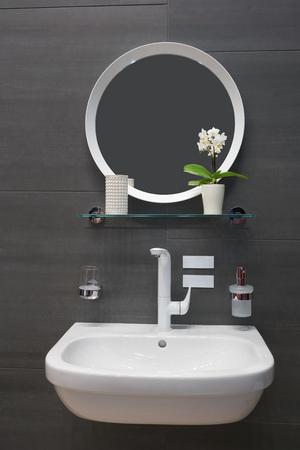 Mirror, white washbasin and white metal water mixer Archivio Fotografico