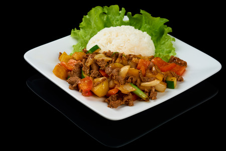 Vietnamese dish Bo Luc Lac (Saute Diced Beef) is a cubed beef sauteed with cucumber, tomatoes, red onion, pepper, and soy sauce. Isolated on black Фото со стока