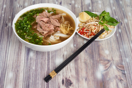 Plate of vietnamese noodle soup Pho bo on wooden background