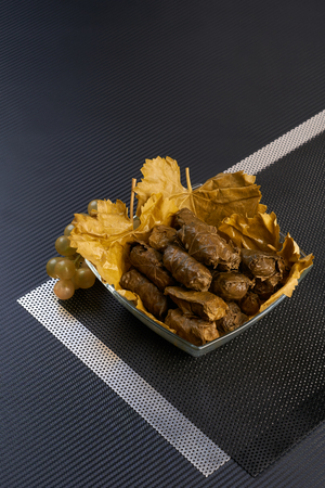 Dolma stuffed grape leaves on metal and carbon backgound