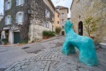 Mougins, France - April 04, 2019: Mougins is a commune in southeastern France that is a great place of tourist attractions. There is a turquoise sculpture of hoofed animal near the church.