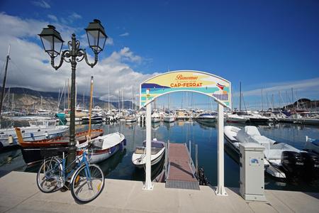 Saint-Jean-Cap-Ferrat, French Riviera, France - April 07, 2019: Sea port of Saint-Jean-Cap-Ferrat. Sign with french text: Welcome to Saint-Jean-Cap-Ferrat.