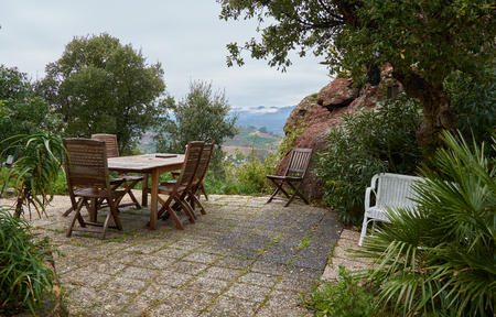 Wooden chairs and table in french garden in April. French Riviera, France