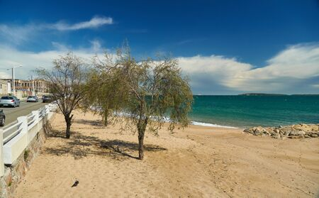 Seascape, sand beach and breakwater in Cannes, French Riviera, France. Boulevard du Midi Louise Moreau is on the left.