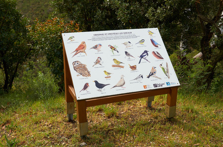 Mandelieu-La Napoule, France - April 04, 2019: Pictures of birds with their names that live in Domaine de Maure-Vieil of French Riviera. Information board calls to observe and protect birds.